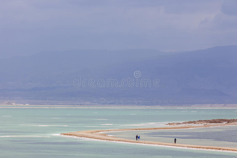 People walking on headland on stormy day at Dead Sea royalty free stock images