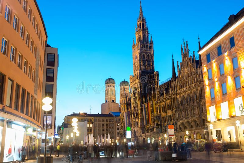 People walking at Marienplatz square and Munich city hall in night in Munich, Germany. Cafes, bars, shops and restaurants. Motion royalty free stock photos