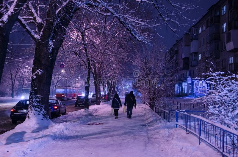 People walking at night home from the Snowy City royalty free stock photography