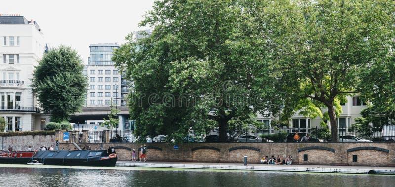 People walking past boats on Regents Canal in Little Venice, London, UK. London, UK - July 18, 2019: People walking past boats on Regents Canal in Little Venice stock images