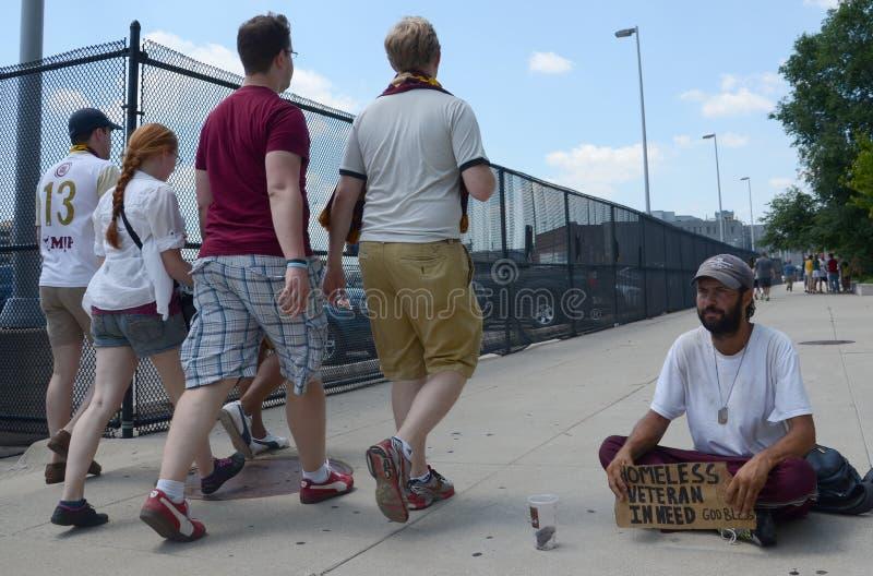 People walking past homeless veteran. DETROIT, MI - JULY 6: People walking past homeless veteran begging for money in Detroit, MI on July 6, 2014 stock image