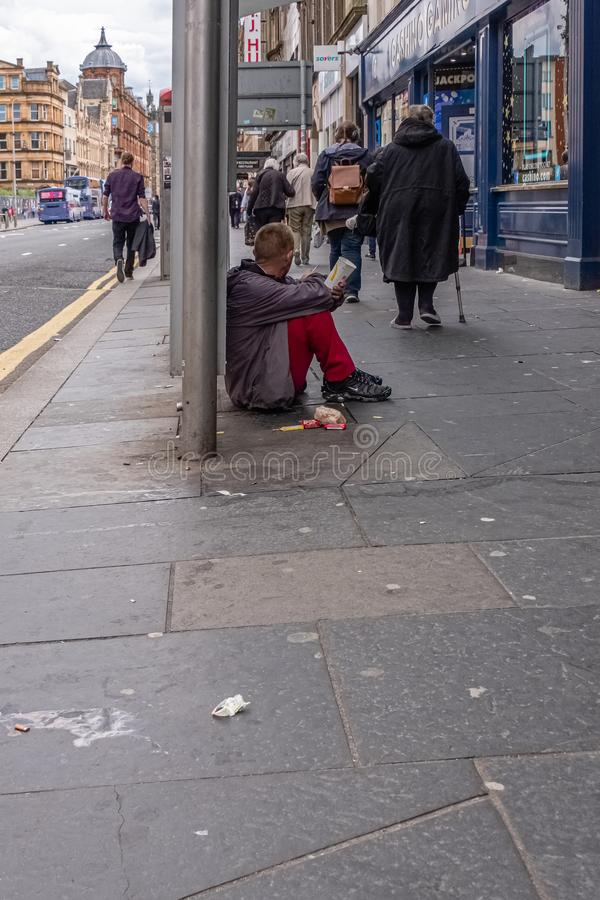 People walking past a male gentleman siting on the Dirty pavement with a McDonald`s  paper cup appealing for money in Glasgow Cit. Glasgow, Scotland, UK - June royalty free stock images