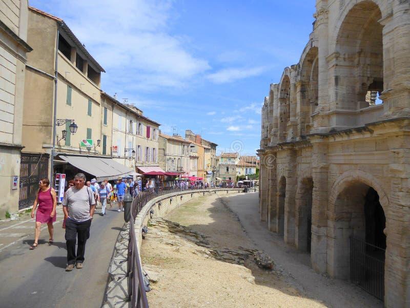People walking past Roman amphitheatre stock images