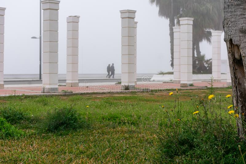 People walking on a promenade. Of columns and palm trees on a foggy winter day royalty free stock images