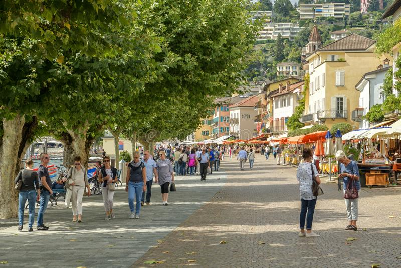 People walking through promenade next to lake Maggiore in Ascona, Switzerland. Ascona, Switzerland - September 2, 2018: People walking through promenade next to royalty free stock image