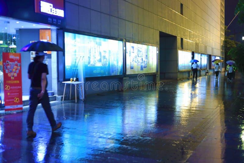 People walking in rain at night stock photo