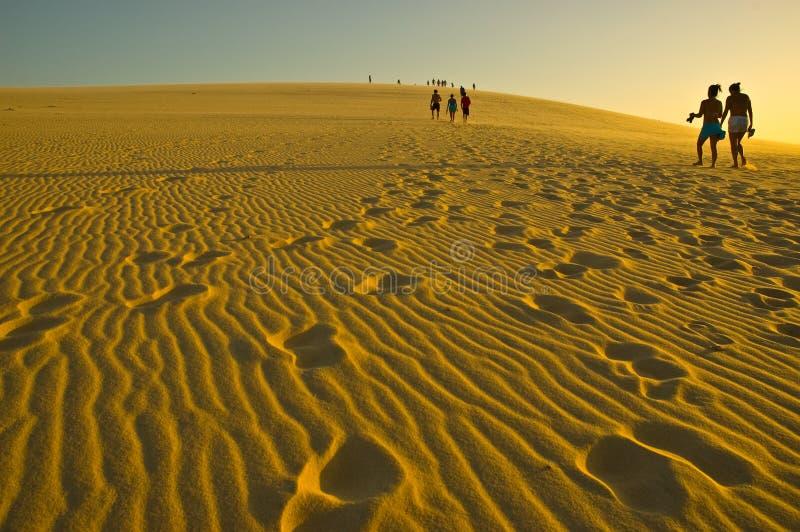 People walking on sand dunes stock photo