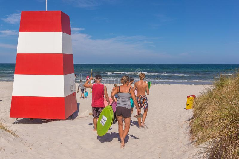People walking in the sand beside a red and white rescuetower. People walking in the sand towards the sea and a red an white rescue tower, Rorvig, Denmark, July stock images
