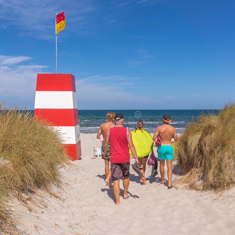 People walking in the sand towards the sea and a rescuetower. People walking in the sand towards the sea and a red an white rescuing tower, Rorvig, Denmark, July royalty free stock photo