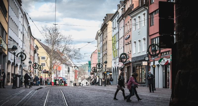 People walking in a shopping street in the historic city center of Freiburg im Breisgau, Germany royalty free stock photo