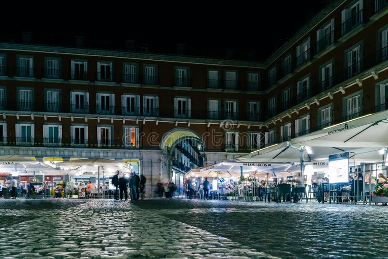 People walking and sitting at restaurant terraces at Plaza Mayor Madrid, Spain at night royalty free stock photo