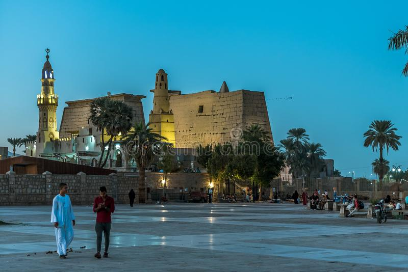 People walking in the square in front of the ancient illuminated Luxor temple at night with dark blue sky and glowing brickwalls stock photos