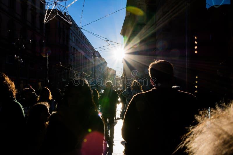 People Walking on Street Sun Flare City Crowd Silhouettes Sidewalk Outdoors Blue Sky Black Anonymous stock photos