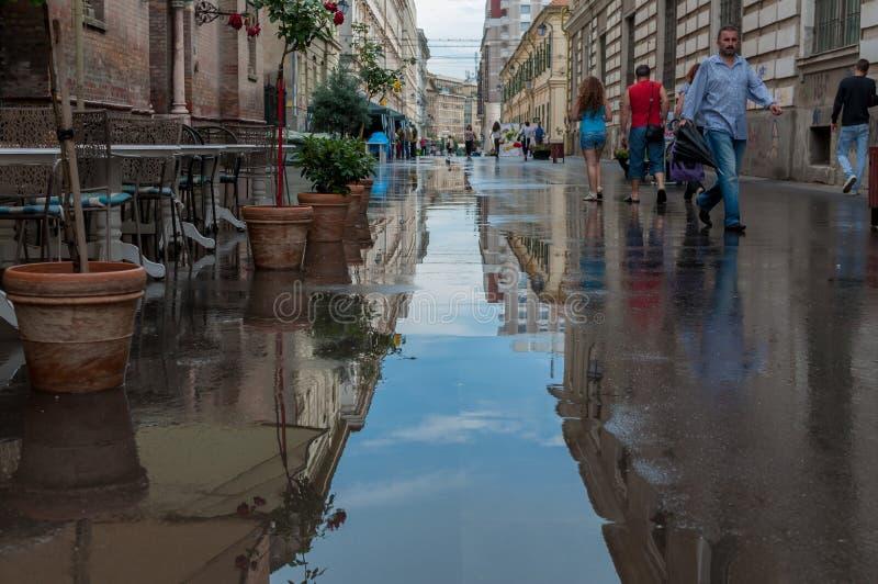 People walking on the street. TIMISOARA, ROMANIA - JULY 23, 2014: People walking on the street. After the rain.  Real people stock photos