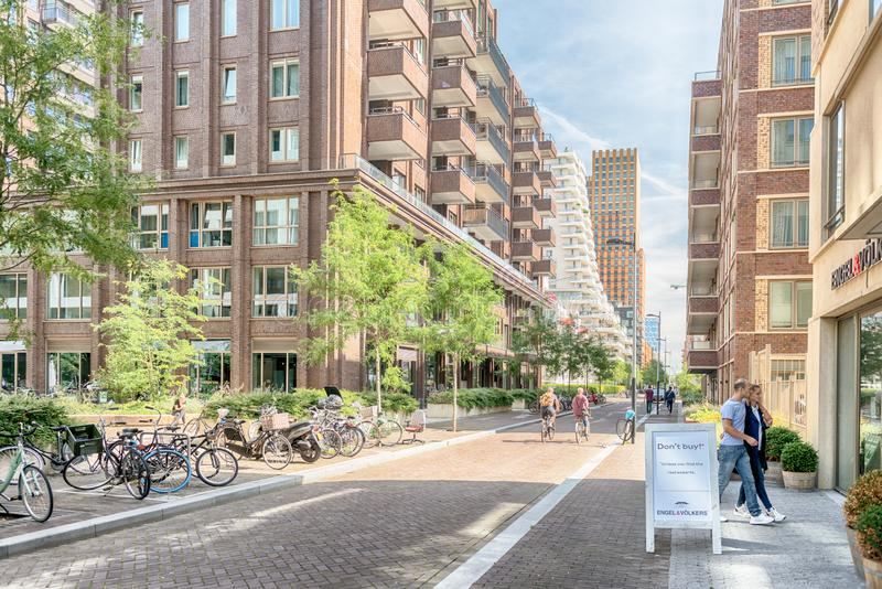 People walking on the streets, luxery apartments at the zuidas in Amsterdam. Amsterdam, George Gershwinlaan, The Netherlands, 08/23/2019, Modern apartments at stock photos