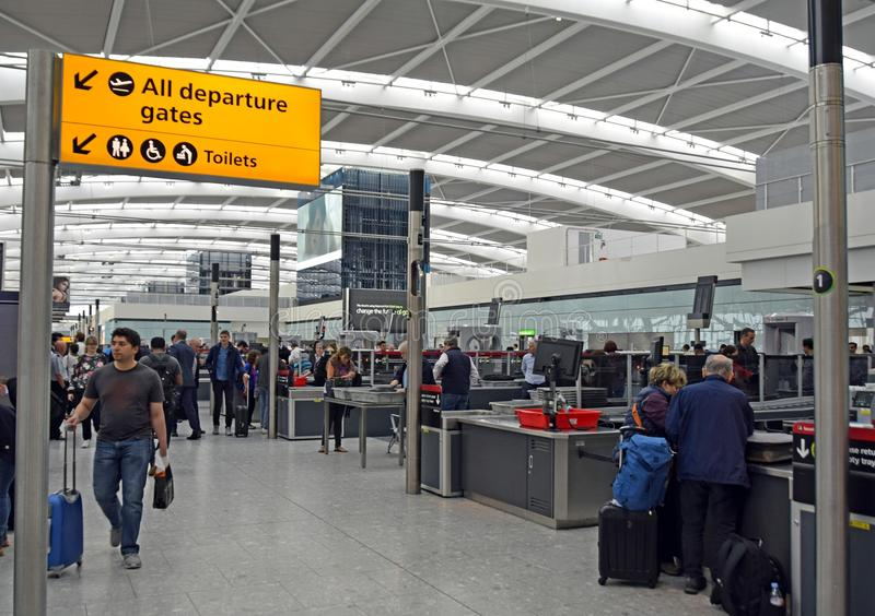 Directional sign Heathrow Airport. People walking with suitcases towards a all departure gates directional sign at Terminal 5 near the Security checkpoint at royalty free stock images