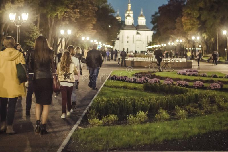 People walking on summer or early autumn park at evening. Long shadows, soft light and low sun. Chernihiv, Ukraine stock image