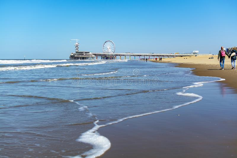 People walking in sunny day on North sea beach in Netherlands near Scheveningen. Tourist and vacation destination in Europe royalty free stock image