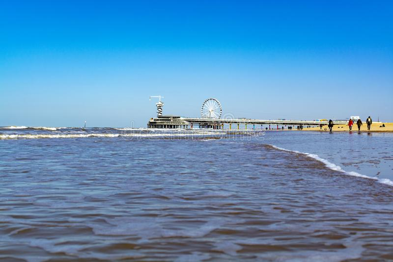 People walking in sunny day on North sea beach in Netherlands near Scheveningen. Tourist and vacation destination in Europe stock photos