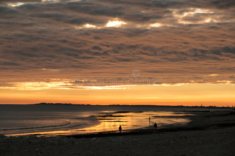 People walking in sunset at the beach, sun reflection on water royalty free stock photography