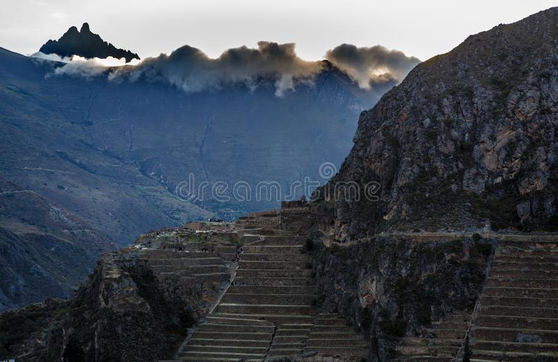 People walking on the terraces of Pumatallis, ancient Inca fortress and mountains covered in clouds, Sacred stock images
