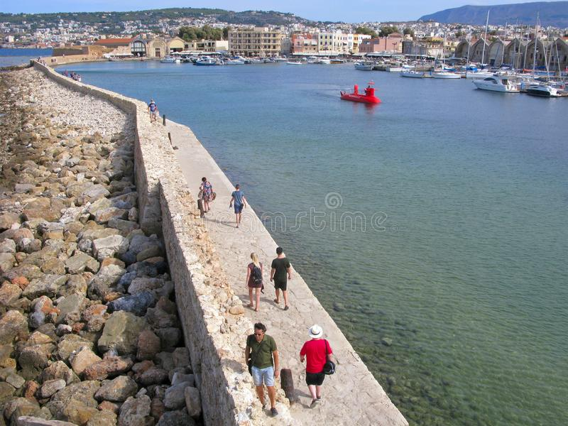 People are walking to old lighthouse in harbor of Chania, Crete, Greece stock photography