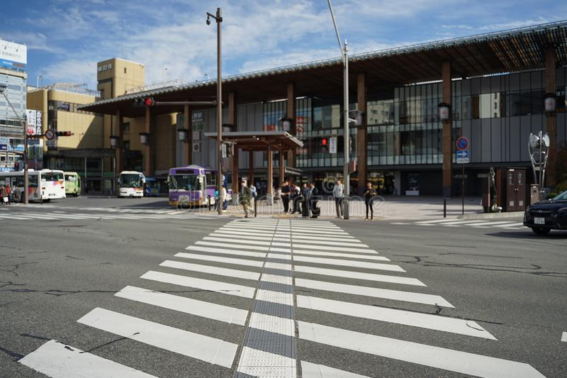 People walking and waiting for the traffic light in front of zebra crossing at The main Nagano train station in the sunny day royalty free stock photo