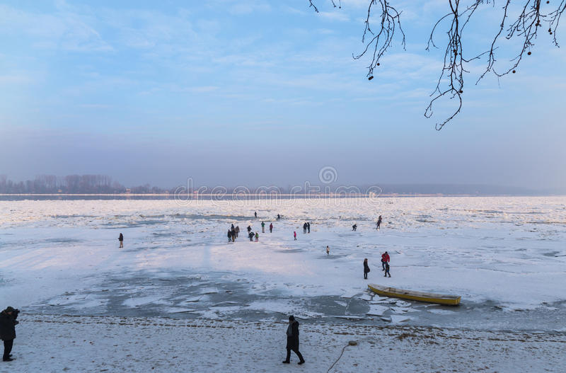 People walks on frozen river. View of part on river Danube when lot of people walks on the frozen river, trapped small fishing boats and beautiful blue sky scape stock images