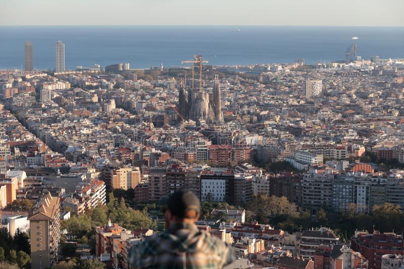 People watch Barcelona view with Sagrada Familia on main term. The city of Barcelona, skyline view from nearby hill of Turo de la Rovira where the constructions royalty free stock photo