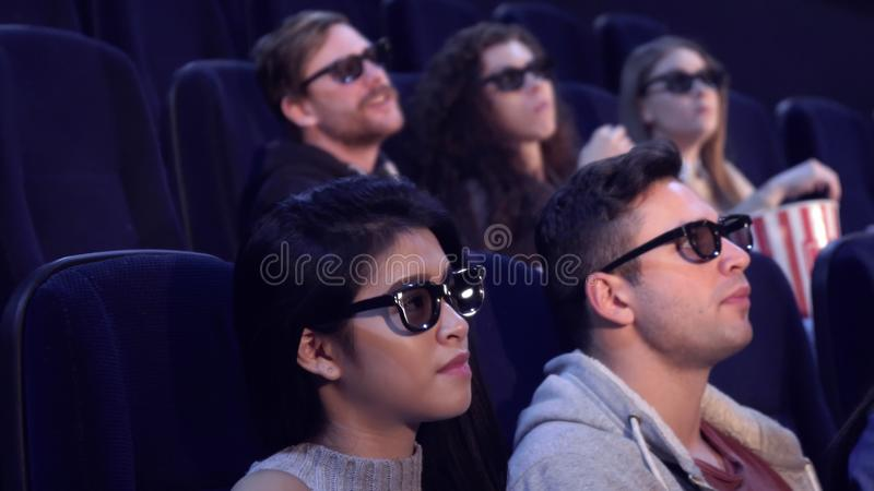 People watch 3D film at the movie theater. Young people watching 3D film at the movie theater. Blond guy pointing his hand on the screen at the cinema. Asian royalty free stock images