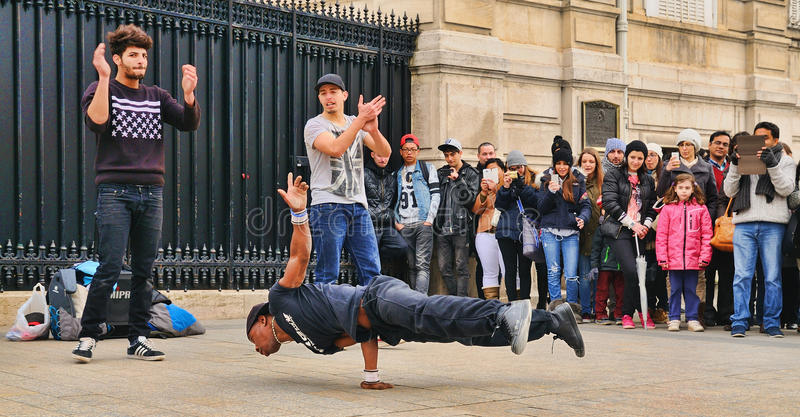 People watch a homeless streetdancer doing breakdance and dance moves in the streets of Paris to earn some money. PARIS - MAR 1: People watch a homeless royalty free stock images