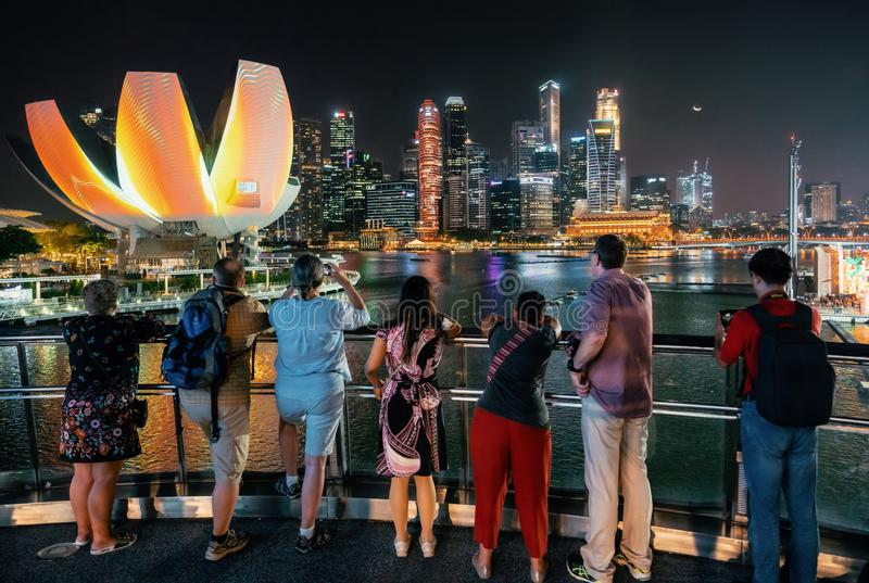 People watch illumintaed cityscape of Singapore stock photography