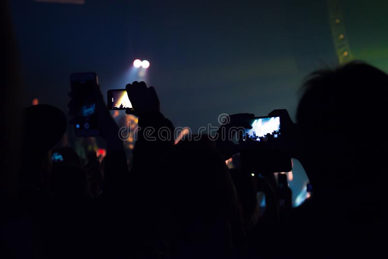 People watching a concert and someone shooting photo and video with a cellphone stock photography