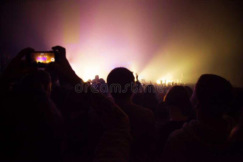 People watching a concert and someone shooting photo and video with a phone royalty free stock images