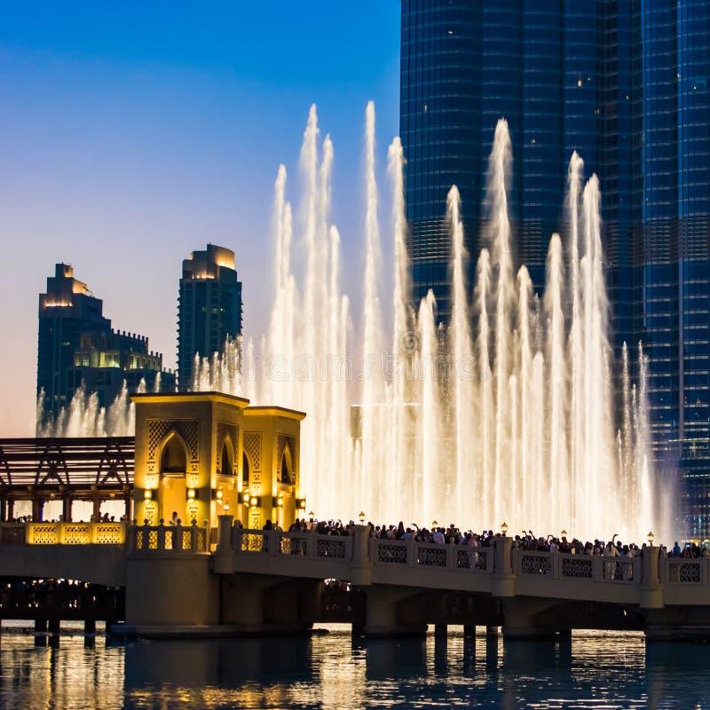 People watching Dubai fountains, illuminated trick fountains at night. Mass tourism at Dubai fountains synchronized show at night, illuminated water garden and stock photography