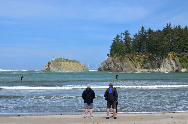 People Watching Paddle Boarder In Sunset Bay State Park, Oregon. Group Of People Standing At The Surf Line Watching Paddle Boarders Surfing royalty free stock photos