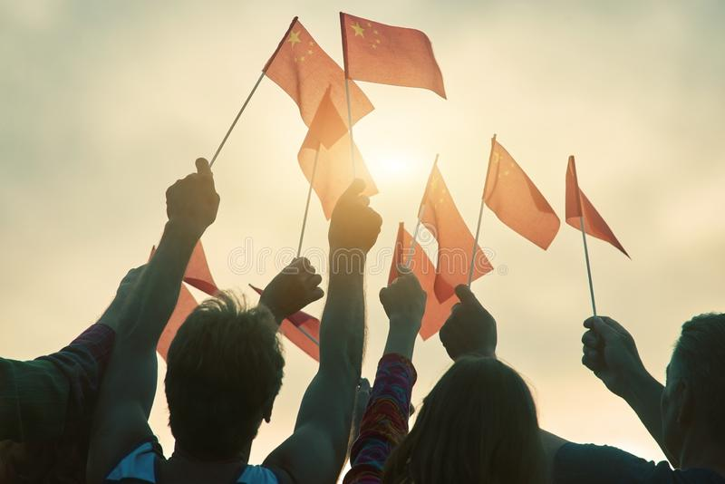 People waving chineese flags. Chineese patriotic family against evening sky background royalty free stock image