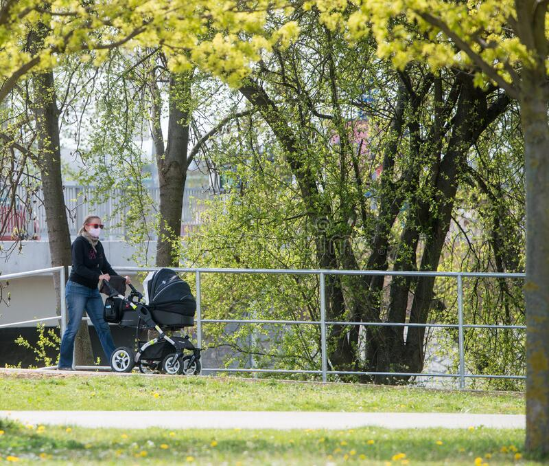 Woman with stroller in the park stock image