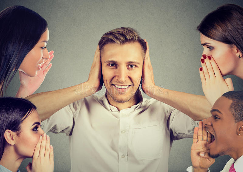 People whispering a secret gossip to a man who covers ears ignoring them. Man and women whispering a secret latest gossip to a happy young men who covers ears stock photography