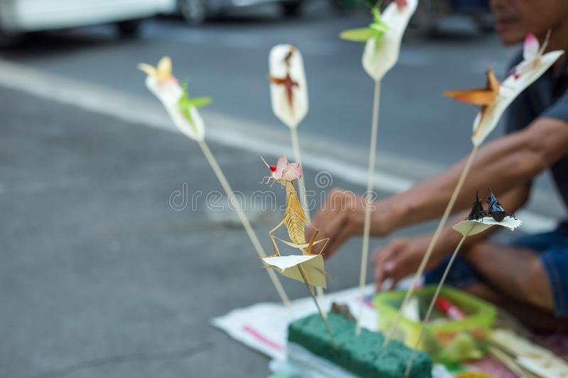 People who make handcraft, folding insects make with palm leafed at wayside stock photography