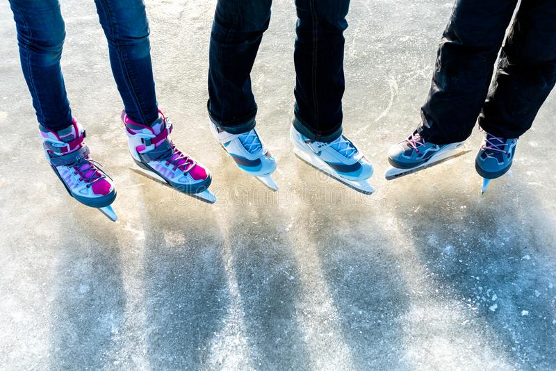 Winter sport and leisure concept - close up of legs of ice skaters on skating rink stock photo