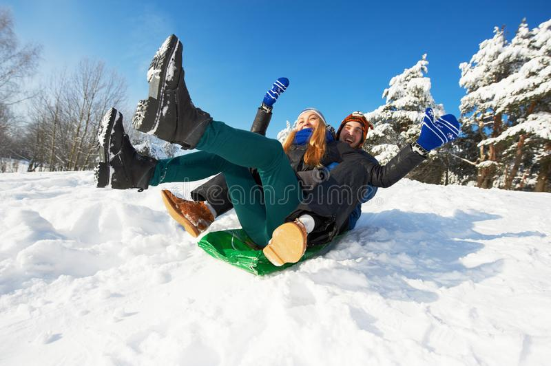 People in winter. young smiling couple sledding. Happy young smiling people sledding at winter snow outdoors royalty free stock photography