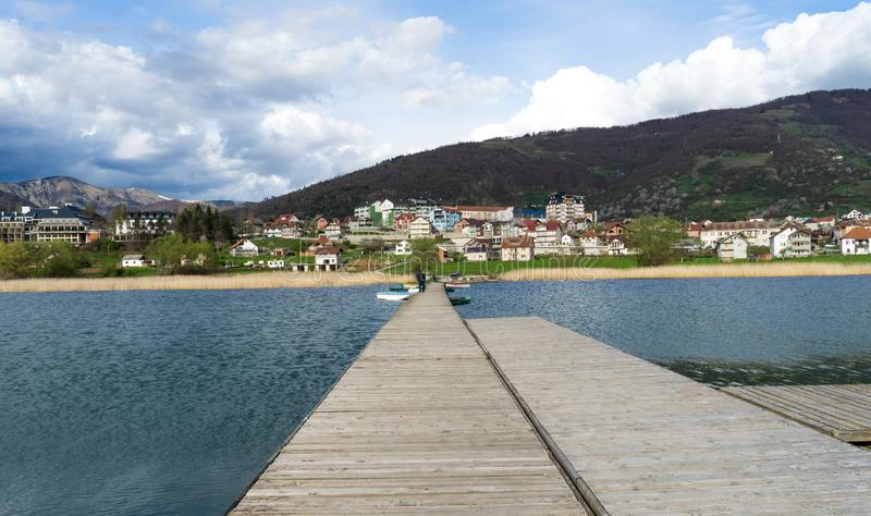 People in wood pier over Plav lake. Fisherman small coast town with ferryboats in Montenegro royalty free stock images