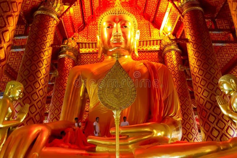 People work with cloth on Buddha image in Wat Phanan Choeng temple in Ayutthaya. AYUTTHAYA, THAILAND - AUG 2016: People work with cloth on Buddha image in Wat stock photo