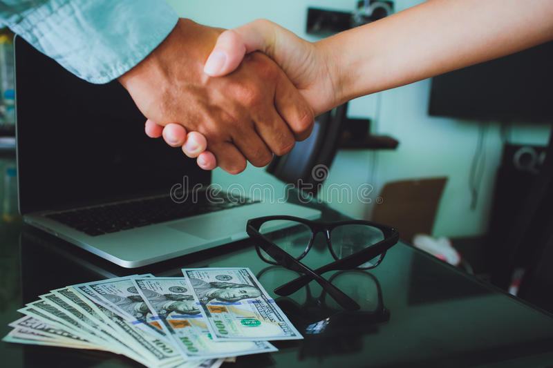 People at work: man and woman hand shaking. glasses , money, lap. People at work: man and woman hand shaking at a meeting. Closeup shot of a two businesspeople royalty free stock photos