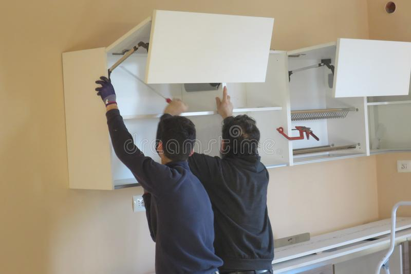 People workers trying to install a kitchen stock images