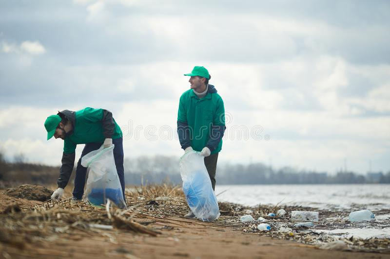 People working on polluted shore stock photos