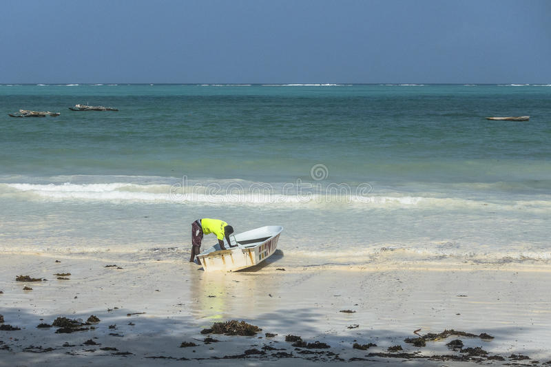 People on Zanzibar beach. Man cleaning boat on tropical beach in Kiwengwa Village on Zanzibar Island. Tanzania , Africa stock images