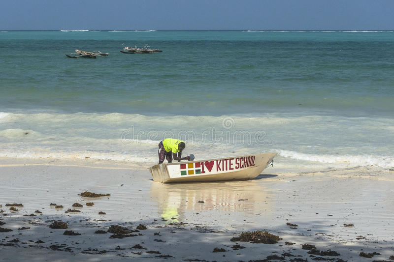 People on Zanzibar beach. Man cleaning boat on tropical beach in Kiwengwa Village on Zanzibar Island. Tanzania , Africa royalty free stock photos