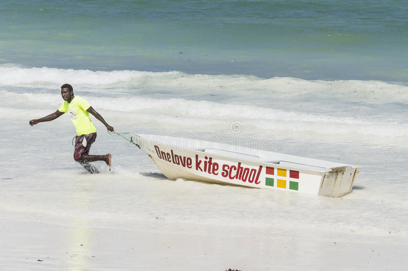People on Zanzibar beach. Man cleaning boat on tropical beach in Kiwengwa Village on Zanzibar Island. Tanzania , Africa stock photo
